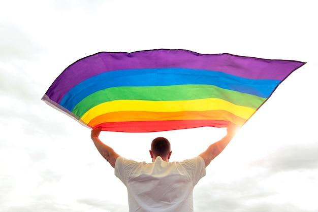 바람에 물결치는 무지개 게이 깃발을 들고 있는 자랑스러운 남자, 인권과 평등에 대한 개념 그림