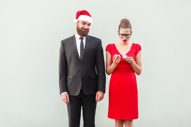 贈り物を探しているクリスマスキャップの誇り高き男。贈り物を持っている欲求不満の女性。スタジオショット、灰色の壁