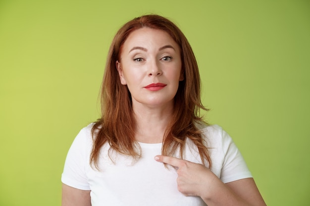 자랑스런 엄마 자신을 가리키는 동기 부여 자신감 빨간 머리 단정적 인 중년 여성이 자신의 능력을 자랑하는 가슴 자원 봉사를 나타내는 카메라 자기 확신 녹색 벽 봐
