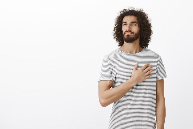 Proud of my country. portrait of handsome thoutful eastern man with beard and curly hair, holding palm on heart and looking away with passionate caring expression