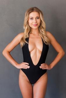 완벽한 몸매를 자랑합니다. 검은 수영복을 입은 매력적인 젊은 금발 머리 여성이 엉덩이에 손을 잡고 회색 배경에 서 있는 동안 카메라를 보고 있습니다.