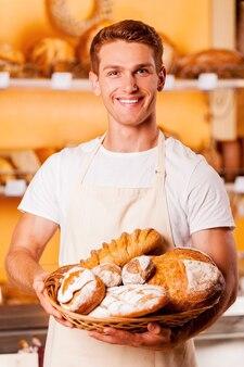 Гордится своей выпечкой. красивый молодой человек в фартуке держит корзину с выпечкой и улыбается, стоя в пекарне