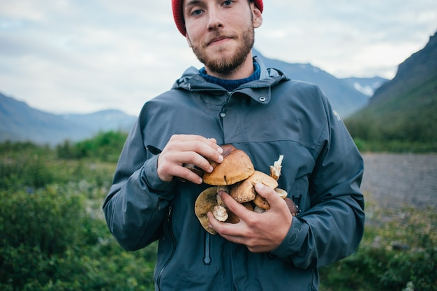 Proud picker man in traditional blue wool sweater with ornaments stands on camping ground in mountains, holds in arms pile of delicious and organic mushrooms