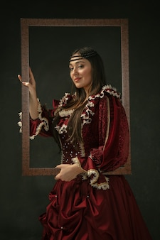 Proud. portrait of medieval young woman in red vintage clothing standing on dark background. female model as a duchess, royal person. concept of comparison of eras, modern, fashion, beauty.