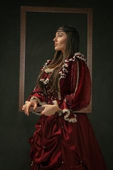 誇りに思う。暗い背景の上に立っている赤い古着の中世の若い女性の肖像画。公爵夫人、王室の人としての女性モデル。時代、現代、ファッション、美しさの比較の概念。