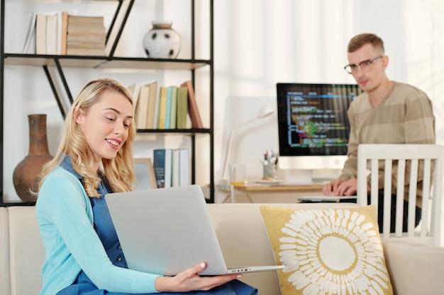 남편에게 그녀의 작업 결과와 노트북 화면을 보여주는 자랑스런 예쁜 젊은 여자