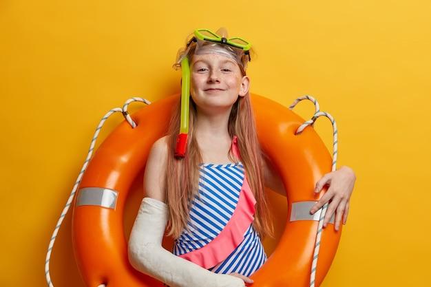 자랑스럽게 만족 한 빨간 머리 소녀가 부풀어 오른 구명 부표로 포즈를 취하고, 스노클링 마스크와 수영복을 착용하고, 바다에서 수영을 즐기고, 사고 후 캐스트에서 팔이 부러지고, 노란색 벽에 서 있습니다.
