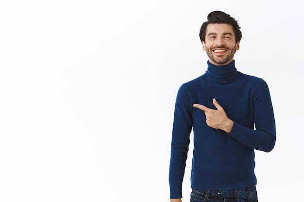 Гордый успешный красивый бородатый бизнесмен в синем стильном свитере с высоким воротом, указывая влево и удовлетворенно улыбаясь, смеясь, хвастаясь купленным новым автомобилем, белая стена