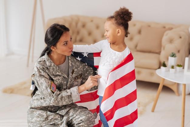 あなたの娘であることを誇りに思います。旗に包まれた彼女の近くに立っている間、彼女の到着時に彼女のお母さんに挨拶する興奮した活気のある素敵な子供