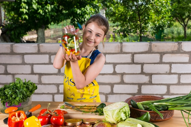 さまざまな食べ物を屋外のテーブルで準備するのに忙しいガラスの瓶に瓶詰めの野菜を披露する誇り高き少女