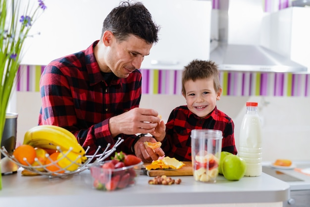 Proud young good looking father and his cute son together in kitchen making smoothie with fresh fruits. healthy eating is important.