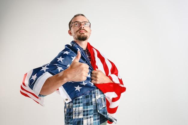 白いスタジオで隔離のアメリカ合衆国の旗を保持している誇り高き青年。