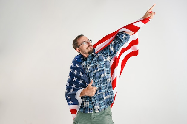 Proud young man holding flag of the united states of america isolated on white studio.