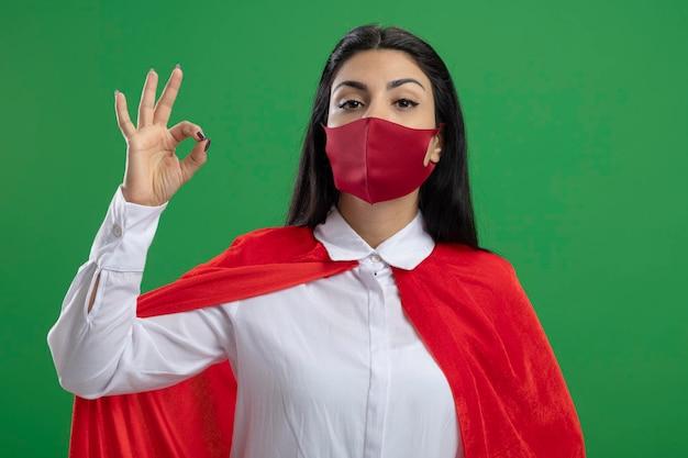 마스크를 쓰고 자랑스럽게 젊은 슈퍼 히어로 여자는 녹색 벽에 고립 된 전면을보고 괜찮아 기호