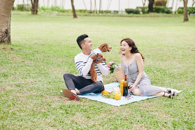 Proud young vietnamese man showing his adorable dog to girlfriend when they are having date in park