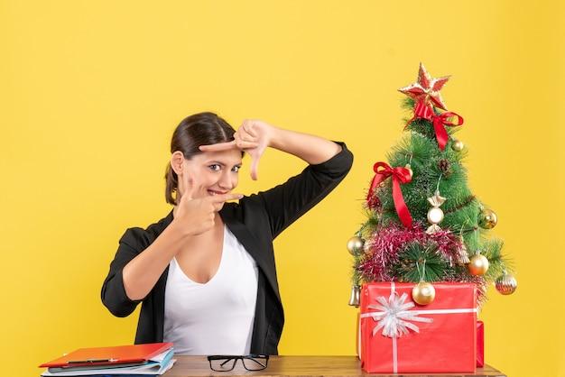 노란색에 사무실에서 장식 된 크리스마스 트리와 소송에서 자랑스럽게 젊은 여자