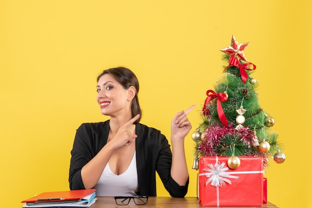 Proud young woman in suit pointing decorated christmas tree at office on yellow