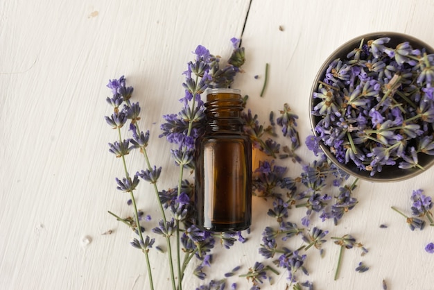 Provencal herbs. lavender oil in a glass bottle. a bowl with flowers on white. flat lay