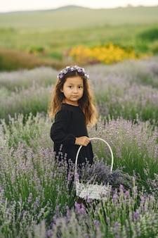 Прованс ребенка расслабляющий в поле лаванды. маленькая леди в черном платье. девушка с сумкой.