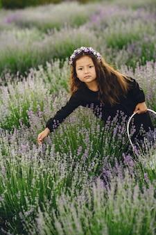 Provenza bambino rilassante nel campo di lavanda. piccola signora in un vestito nero. ragazza con borsa.