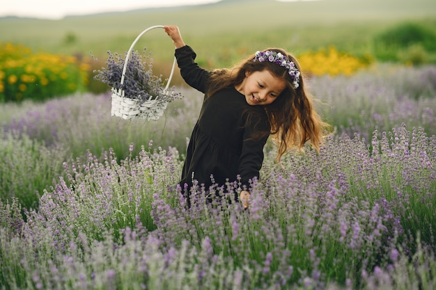 Provence child relaxing in lavender field. little lady in a black dress. girl with bag.