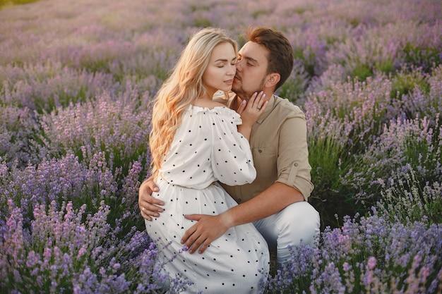 ラベンダー畑でリラックスしたプロヴァンスのカップル。白いドレスの女性。