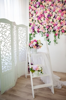 Provence-style interior with a white screen, bright floral wall, bucket with artificial flowers