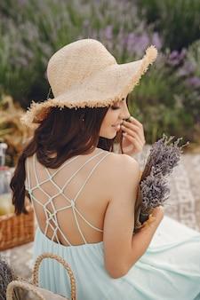 ラベンダー畑でリラックスしたプロヴァンスの女性。青いドレスと麦わら帽子の女性。