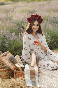 ラベンダー畑でリラックスしたプロヴァンスの女性。ピクニックの女性。花の花輪の女性。