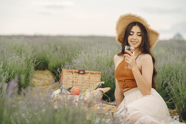 Женщина прованса расслабляющий в поле лаванды. дама на пикнике.