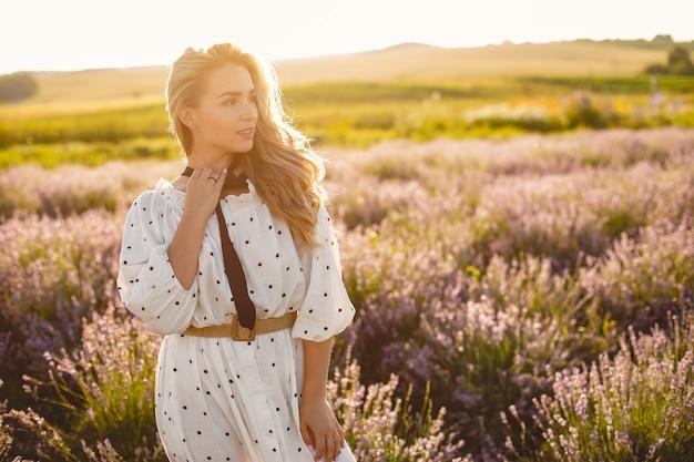 Женщина прованса расслабляющий в поле лаванды. дама в белом платье. девушка в соломенной шляпе.