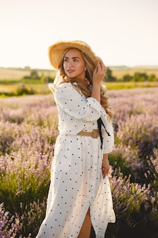 라벤더 밭에서 편안한 프로방스 여자입니다. 흰 드레스 아가씨. 밀짚 모자 소녀입니다.