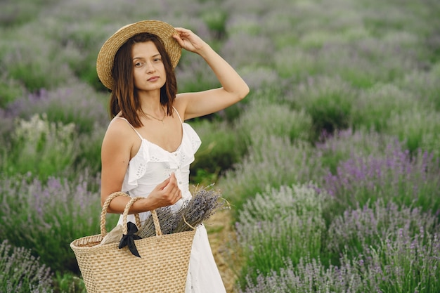 ラベンダー畑でリラックスしたプロヴァンスの女性。白いドレスの女性。バッグを持つ少女。