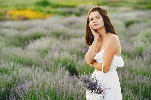 라벤더 밭에서 편안한 프로방스 여자입니다. 흰 드레스 아가씨. 가방 소녀.