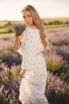 ラベンダー畑でリラックスしたプロヴァンスの女性。白いドレスの女性。花の花束を持つ少女。