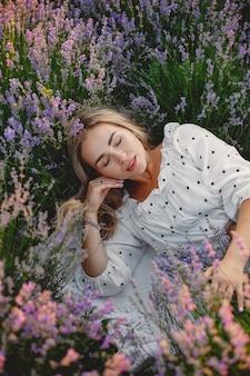 Женщина прованса расслабляющий в поле лаванды. дама в белом платье.