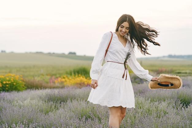 ラベンダー畑でリラックスしたプロヴァンスの女性。白いドレスの女性。