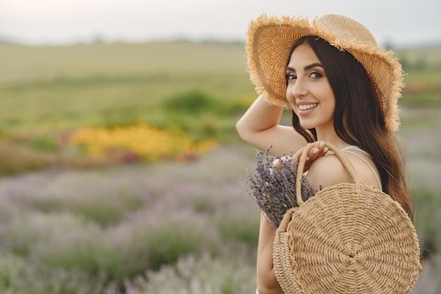 Женщина прованса расслабляющий в поле лаванды. дама в соломенной шляпе. девушка с сумкой.