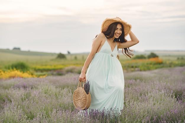 라벤더 밭에서 편안한 프로방스 여자입니다. 밀짚 모자를 가진 아가씨. 가방 소녀.