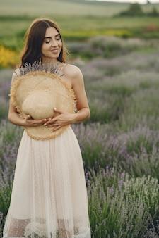 ラベンダー畑でリラックスしたプロヴァンスの女性。麦わら帽子の女性。