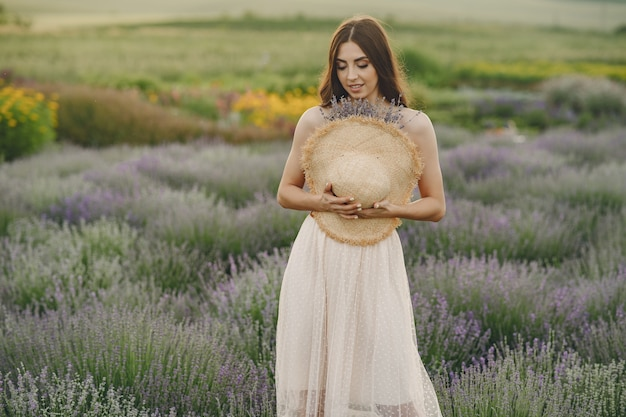 Женщина прованса расслабляющий в поле лаванды. дама в соломенной шляпе.