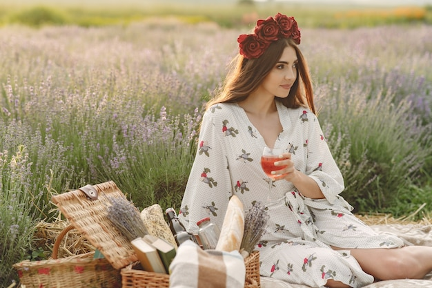 Provence woman relaxing in lavender field. lady in a picnic. woman in a wreath of flowers.