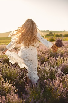 Provence woman relaxing in lavender field. lady in a white dress. girl with bouquete of flowers.