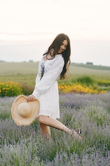Provence woman relaxing in lavender field. lady in a white dress.