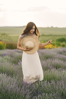 Provence woman relaxing in lavender field. lady with a straw hat.