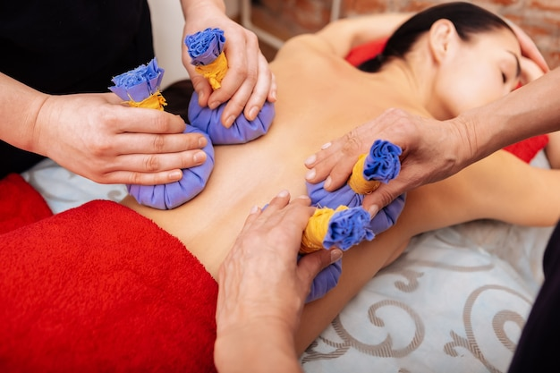 Providing massage. experienced workers carrying blue herbal bags on back of sleeping client