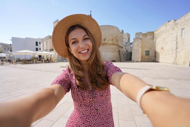 Концепция туризма близости. улыбающаяся женщина, делающая автопортрет в апулии со старым городом отранто на заднем плане, италия