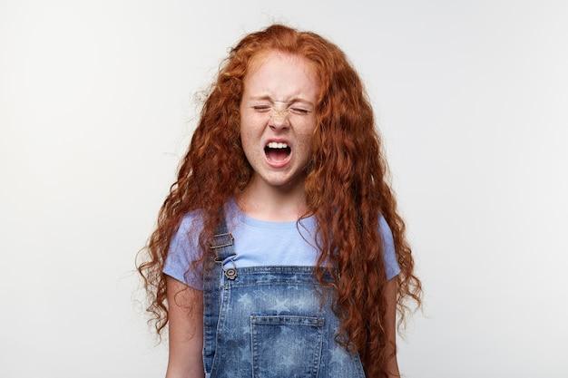 Prtrait di sceaming lentiggini bambina con i capelli rossi, si trova su un muro bianco con gli occhi chiusi e la bocca spalancata, sembra infelice e piange.