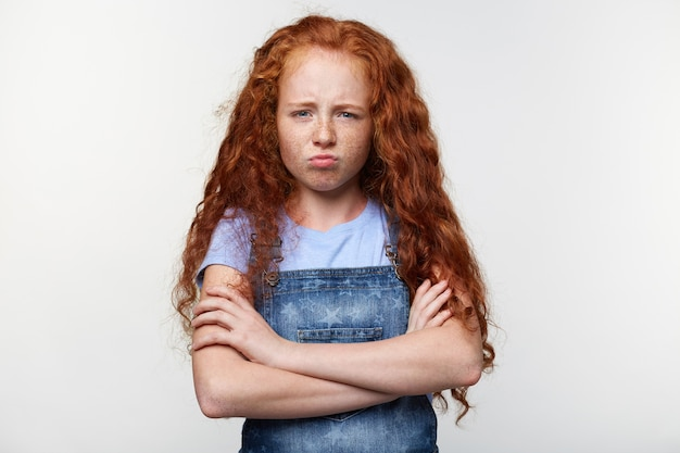 Prtrait of unhappy freckles little girl with ginger hair, stands over white wall with crossed arms, looks sad and offended.