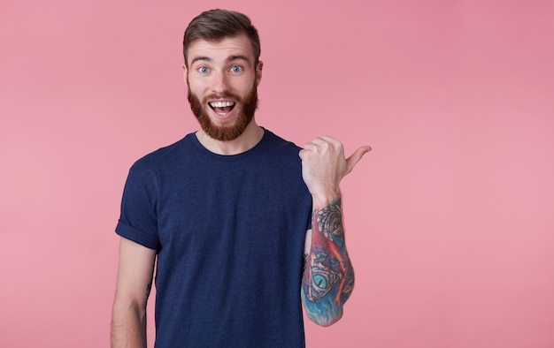 Prttrait молодого счастливого рыжебородого молодого парня с широко открытым ртом от удивления, в синей футболке, указывающего пальцем, чтобы скопировать пространство справа, изолированное на розовом фоне.